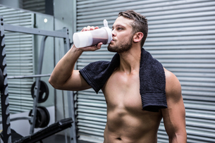 Muscular man drinking protein cocktail FYI00009253