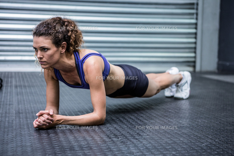 Muscular woman doing push-ups FYI00009269