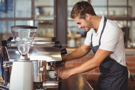 Handsome barista making a cup of coffee FYI00009639