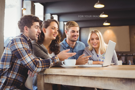 Smiling friends drinking coffee and pointing on laptop screen FYI00009668