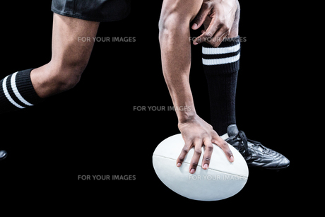 Low section of sportsman holding rugby ball FYI00009712