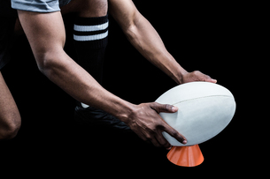 Cropped image of sportsman keeping rugby ball on kicking teeの素材 [FYI00009719]