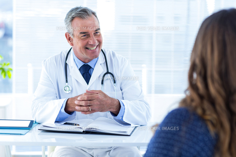 Smiling male doctor with woman in clinic FYI00009732