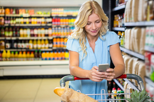 Smiling woman with cart using smartphone FYI00009901