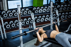 Fit woman lifting barbell while lying on bench FYI00010174