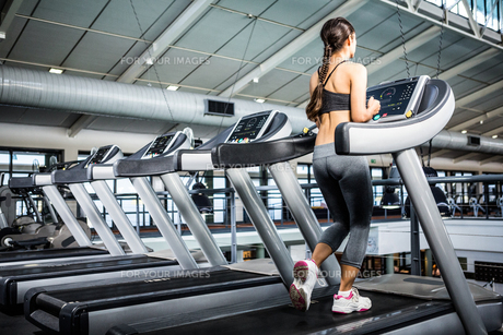 Rear view of woman jogging in treadmill FYI00010175
