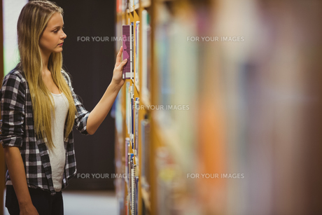 Blonde student reading book next to bookshelf FYI00010298