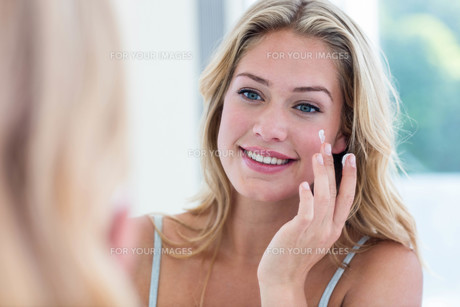 Smiling pretty woman applying cream on her face FYI00010464