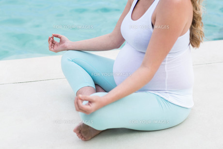 Pregnant woman doing yoga FYI00010469
