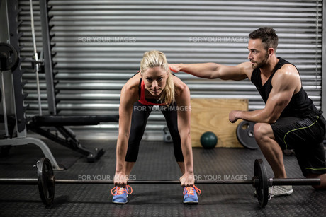 Trainer helping woman with lifting barbell FYI00010485
