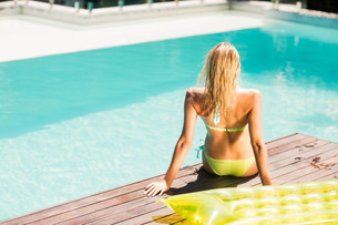 Peaceful blonde sitting on pools edge FYI00010511