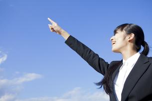 空に指を指すビジネスウーマン FYI00024563