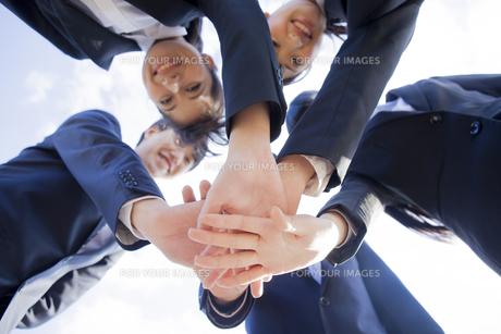 手を重ねるビジネスマンとビジネスウーマン FYI00024564