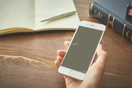 デスクでスマートフォンを使う女性 FYI00024943