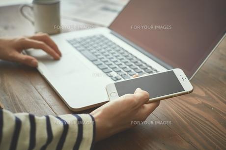 カフェでパソコンとスマートフォンを使う女性 FYI00024947