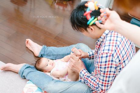 パパが赤ちゃんをあやす姿をみつめながらママもおもちゃであやしてる姿 FYI00024960