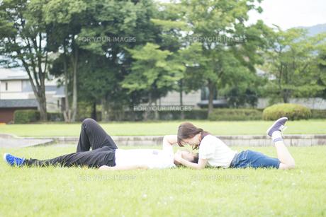 芝生で寝ころび見つめあうカップルの素材 [FYI00024999]