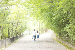 風と緑を感じながら道を歩くカップル FYI00025000