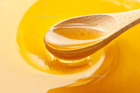 木のスプーンでかき混ぜる蜂蜜 FYI00025529