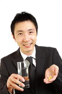 サプリを飲むビジネスマン FYI00036140