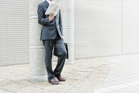 屋外で新聞を読むビジネスマン FYI00040156