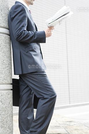 屋外で新聞を読むビジネスマン FYI00040410