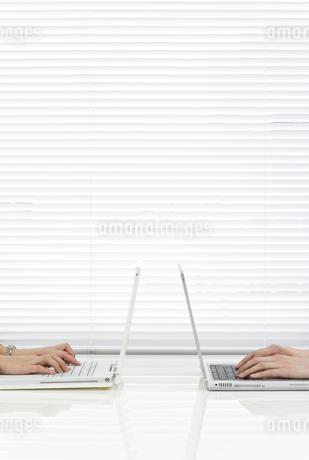 向かい合ってパソコンをする男女の社員 FYI00040767