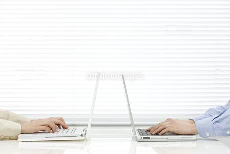 向かい合ってパソコンをする男女の社員 FYI00040771