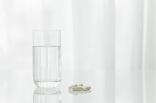 テーブルに置かれた薬とコップ FYI00040826