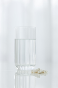 テーブルに置かれた薬とコップ FYI00040827