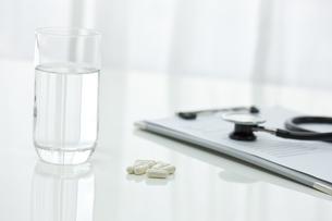 テーブルに置かれた薬とコップ FYI00040839
