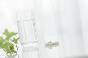 テーブルに置かれた薬とコップ FYI00040884