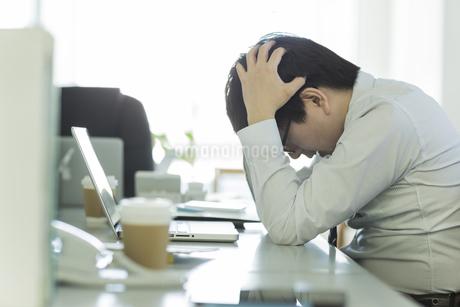頭を抱えながら嘆くビジネスマン FYI00042847