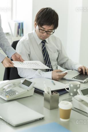 資料を確認するビジネスマンたち FYI00042850