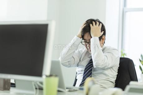 頭を抱えながら嘆くビジネスマン FYI00042862