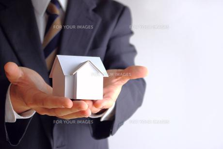 家の模型を差し出すビジネスマン FYI00073205