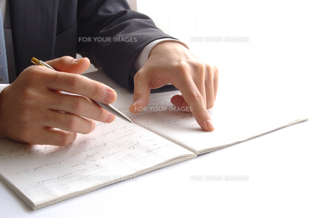 ノートの文字を指差すビジネスマン FYI00073227