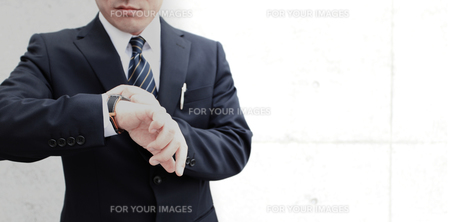 腕時計を見るビジネスマン FYI00107889