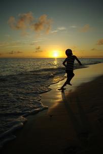 夕暮れの波打ち際で遊ぶ子供 FYI00117301