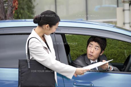 車内の上司に書類を渡す若い女性社員 FYI00118193