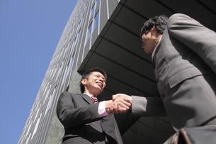 オフィス街で握手をするビジネスマン FYI00118209