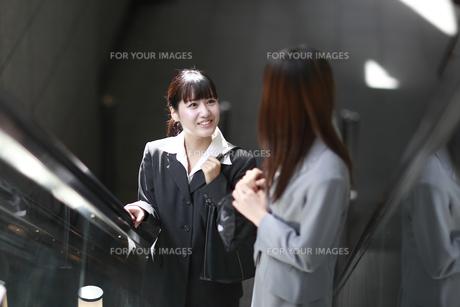 エスカレーターで話す若いビジネスウーマン FYI00118246