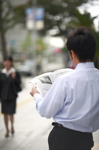 新聞を読むビジネスマンの後ろ姿 FYI00118268