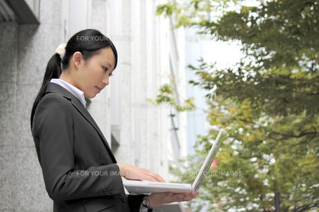 屋外でノートパソコンを開く若い女性 FYI00118299