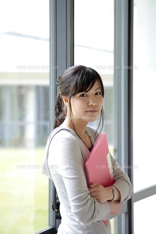 ファイルを手に持つ女子学生 FYI00118332