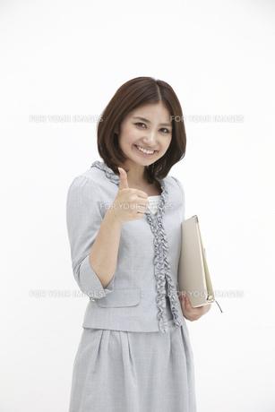 親指を立てサインを送るビジネスウーマン FYI00118501