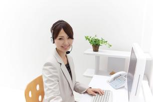 インカムをつけパソコンを操作するビジネスウーマン FYI00118530