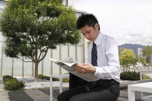 屋外で新聞を読む若いビジネスマン FYI00119217