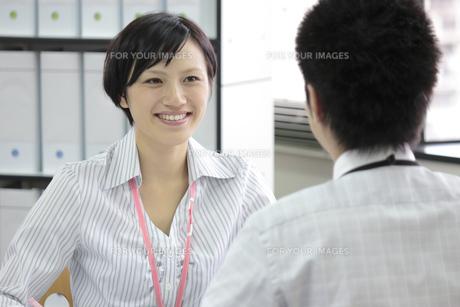 笑顔で上司と話すビジネスウーマン FYI00119263