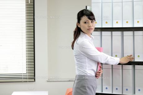 棚からファイルを取り出すビジネスウーマン FYI00119413
